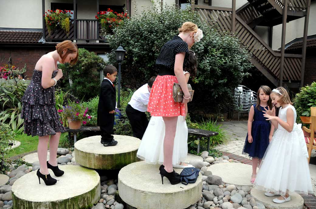Unusual and interesting wedding photo of children playing on the stone water fountains in the courtyard garden at Brook Kingston Lodge Hotel Surrey