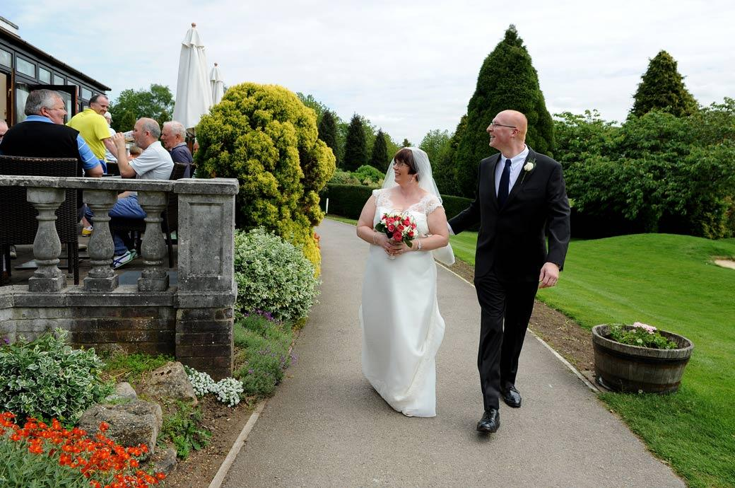 Bride and Groom responding to the golfing well wishers as they walk down the terrace in this wedding photo taken in Surrey at Kingswood Golf Club in leafy Tadworth