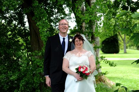 Married couple take a break from the marriage celebrations for a romantic walk amongst the trees in this wedding photo from Kingswood Golf Club a popular Surrey wedding venue