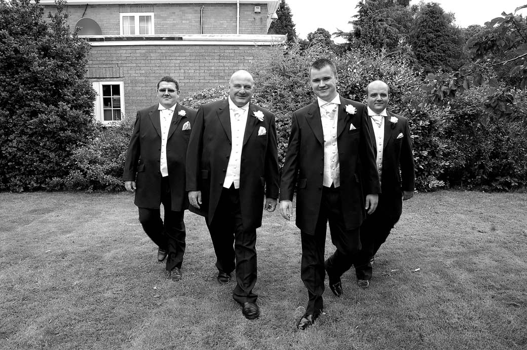 Groom and his groomsmen walking across the lawn in this relaxed pre wedding photograph taken before leaving for Kingswood Golf Club a popular Surrey wedding venue