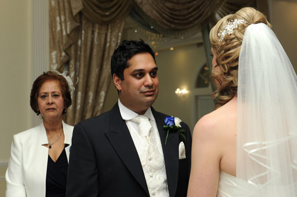 The Groom looks intently with loving eyes at his Bride as she says her marriage vows in this wedding photograph taken at Kingswood Golf Club Surrey in the Ballroom ceremony