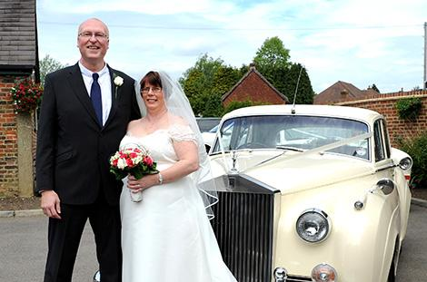 Happily married couple strike a pose in front of their classic cream Rolls Royce wedding car at Surrey venue Kingswood Golf Club in the village of Tadworth