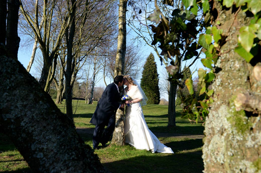 A romantic kiss caught through the trees by a Surrey Lane wedding photographer during a walk through the green and tranquil grounds of Kingswood Golf Club