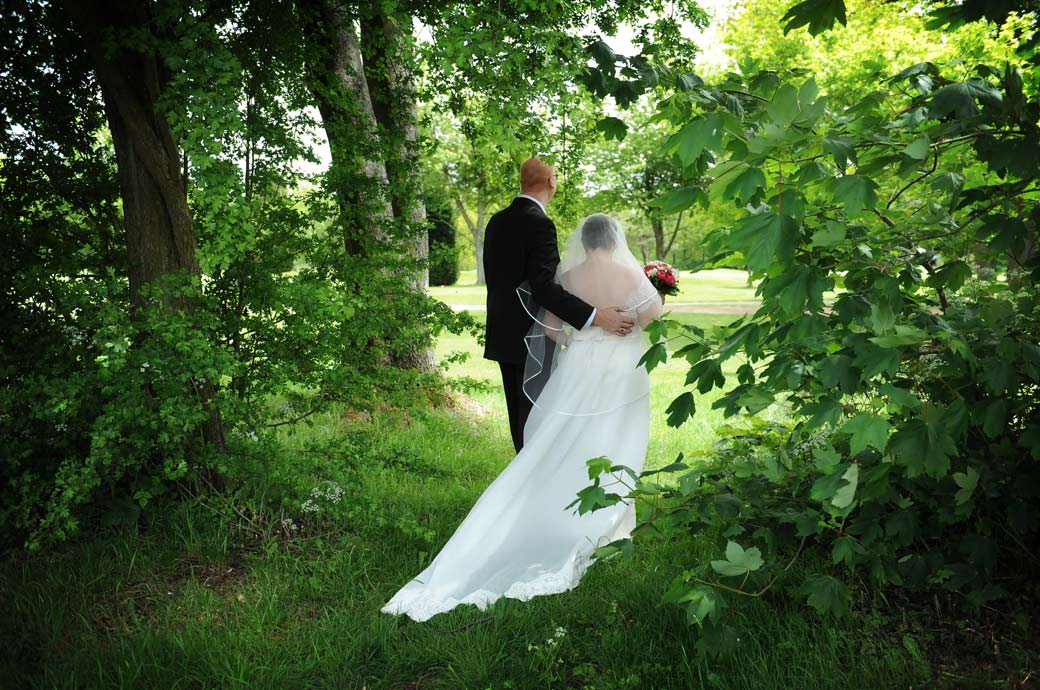 Bride and groom standing under the cover of the green leafy trees and looking out over the golf greens at Kingswood Golf Club a relaxed wedding view in Tadworth Surrey