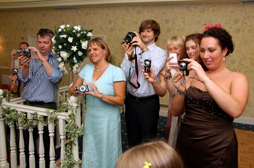 Wedding guests get their cameras out to capture the Bride and groom cutting the wedding cake in Tadworth Surrey at Kingswood Golf Club in The Conservatory