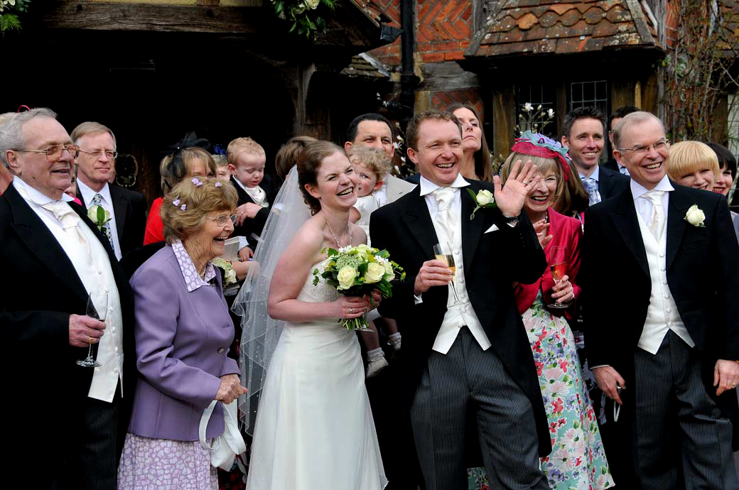 A lovely happy laughing Bride and Groom wedding picture taken with all their guests at the boutique wedding venue in Surrey Langshot Manor
