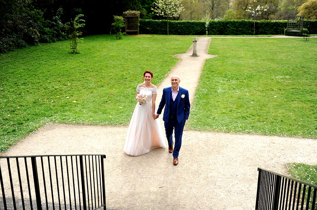 Relaxed looking Bride and Groom walking hand in hand at Surrey wedding venue Leatherhead Register Office look up at smile at family and guests on the terrace