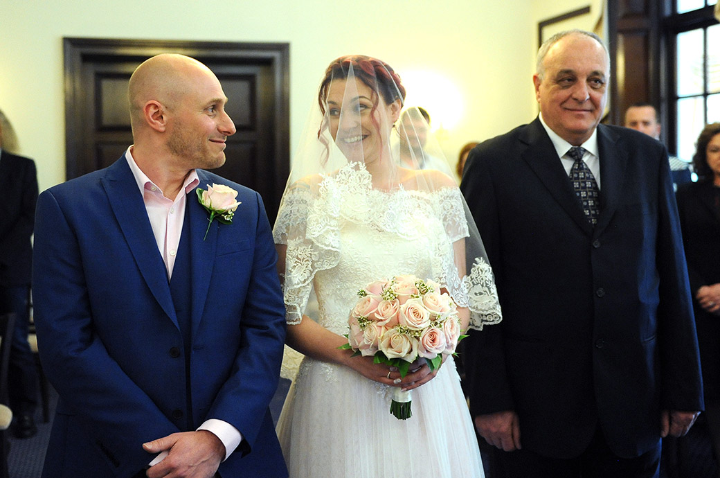 Excited Bride looks over to her smiling Groom as they stand at the end of the aisle in The State Room at Leatherhead Register Office in Surrey