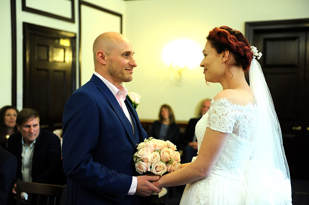 An excited bride and groom captured in the State Room at Surrey wedding venue Leatherhead Registry Office as they lovingly look into each other's eyes and hold hands