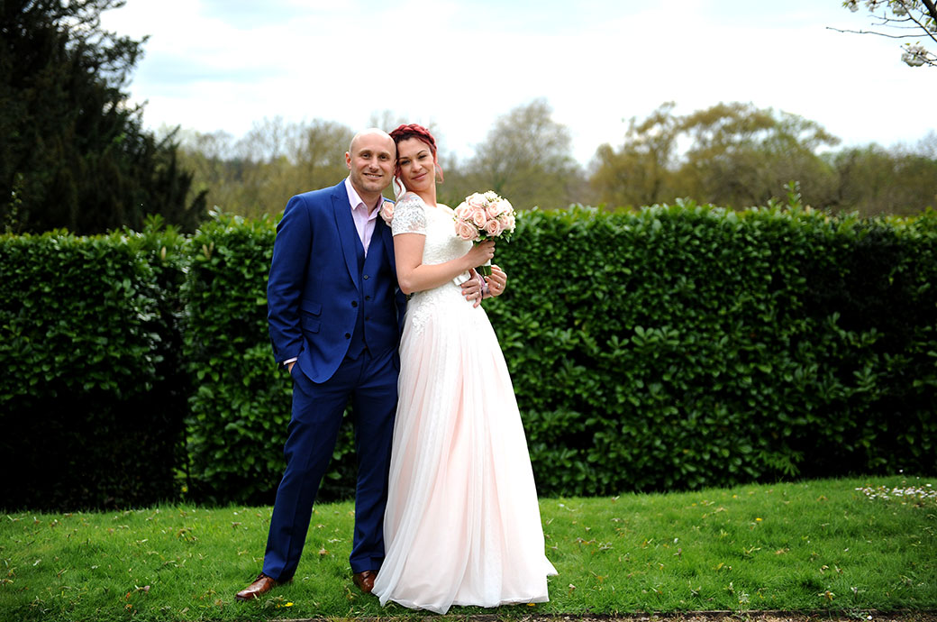 Handsome newlywed couple look relaxed at the popular wedding venue Leatherhead Registry Office as they pose for their Surrey Lane wedding photographer