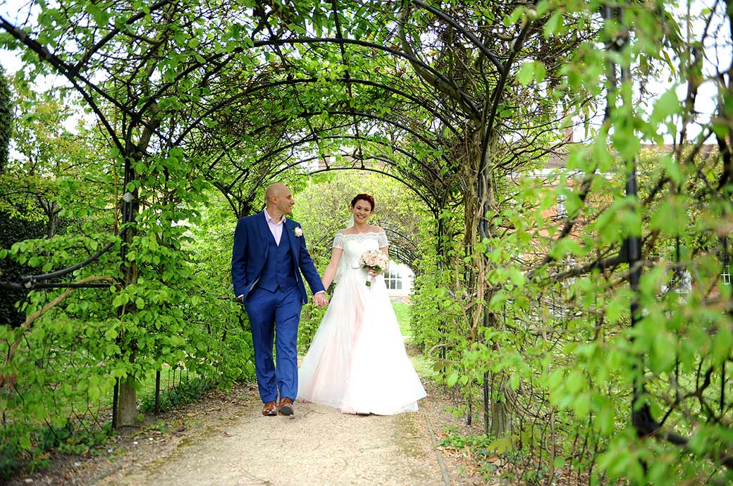 Happy smiling Bride is lead by her Groom in a walk down through the green arbour at the lovely Leatherhead Register Office in Surrey