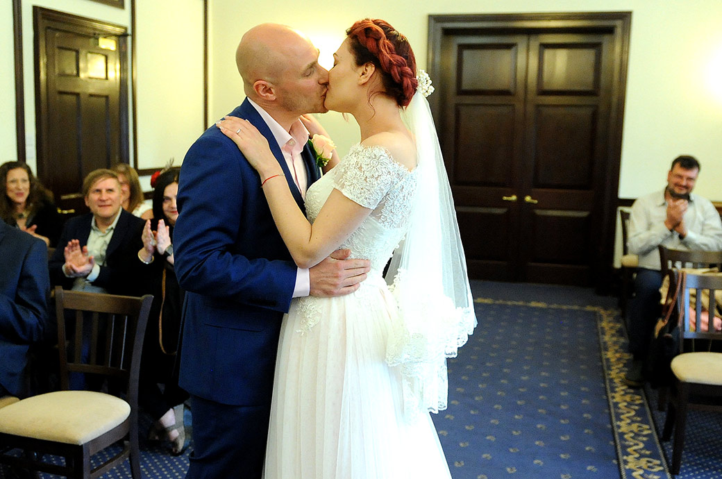Bride and groom captured in The State Room at Surrey wedding venue Leatherhead Register Office as they passionately kiss after being named husband and wife