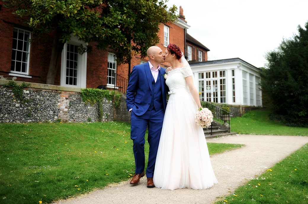 A natural loving moment captured at the popular wedding venue Leatherhead Registry Office in Surrey as the newlyweds stroll along the garden path and kiss