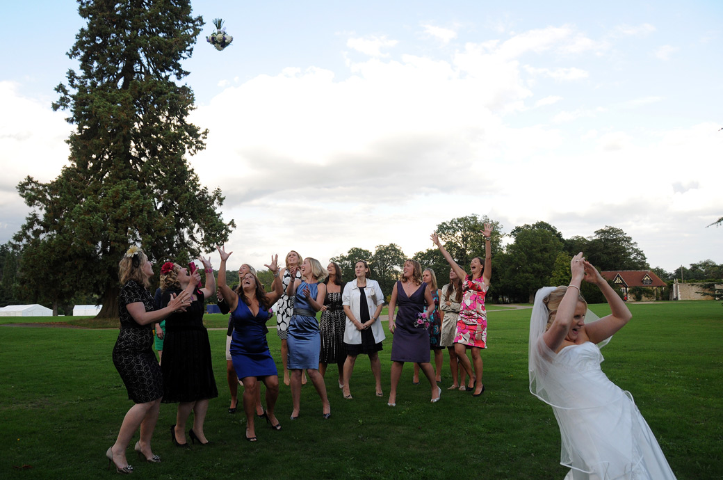 Ladies jumping up to catch the Bride's bouquet in this wonderfully atmospheric wedding photo taken on the lawn near the Tithe Barn at Surrey wedding venue Loseley Park