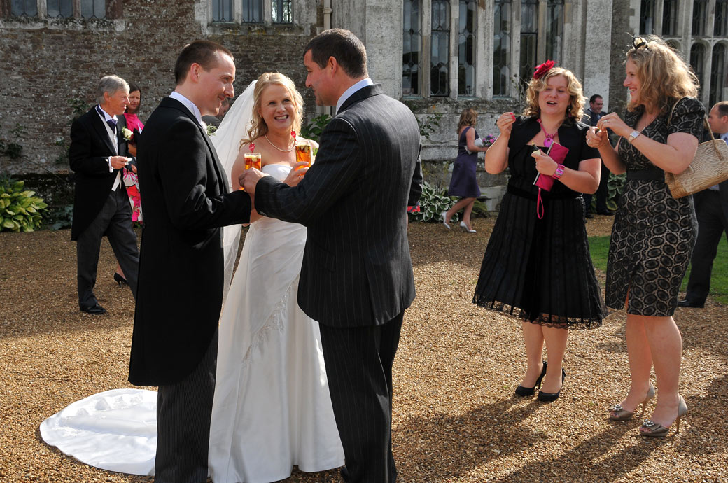 Happy newly-weds chatting with Pimms wedding picture captured on the lawn outside the wonderful 14th Century Elizabethan Mansion Loseley Park a fine wedding venue in Surrey