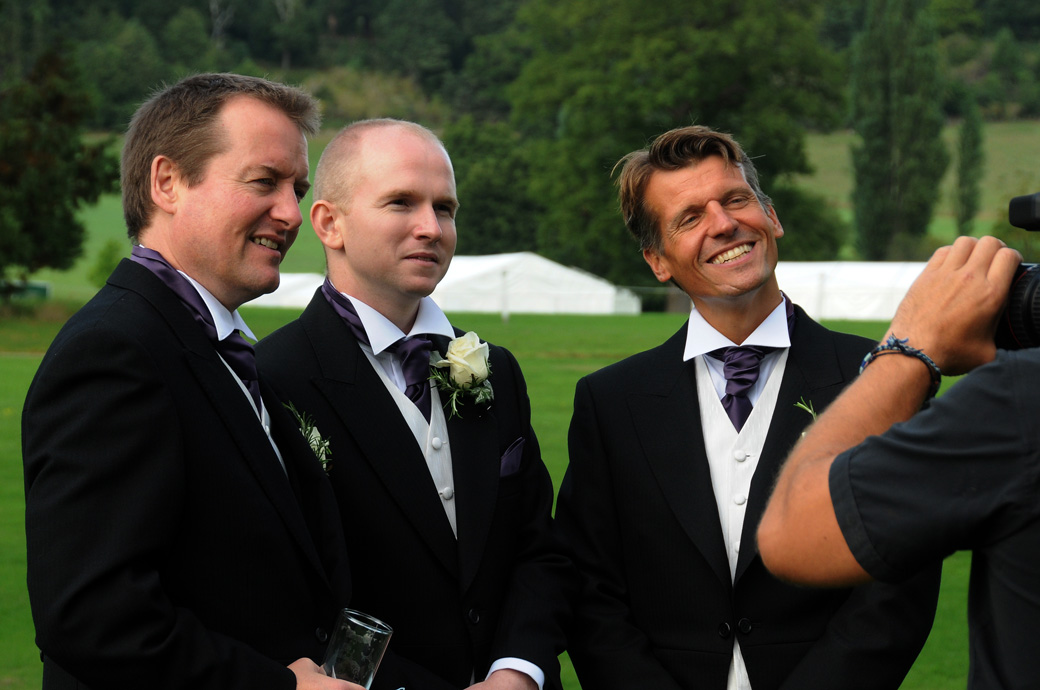 Groomsmen chatting to and being filmed by a videographer in this relaxed wedding photo taken at the Surrey wedding venue Loseley Park during a reception on the lawn