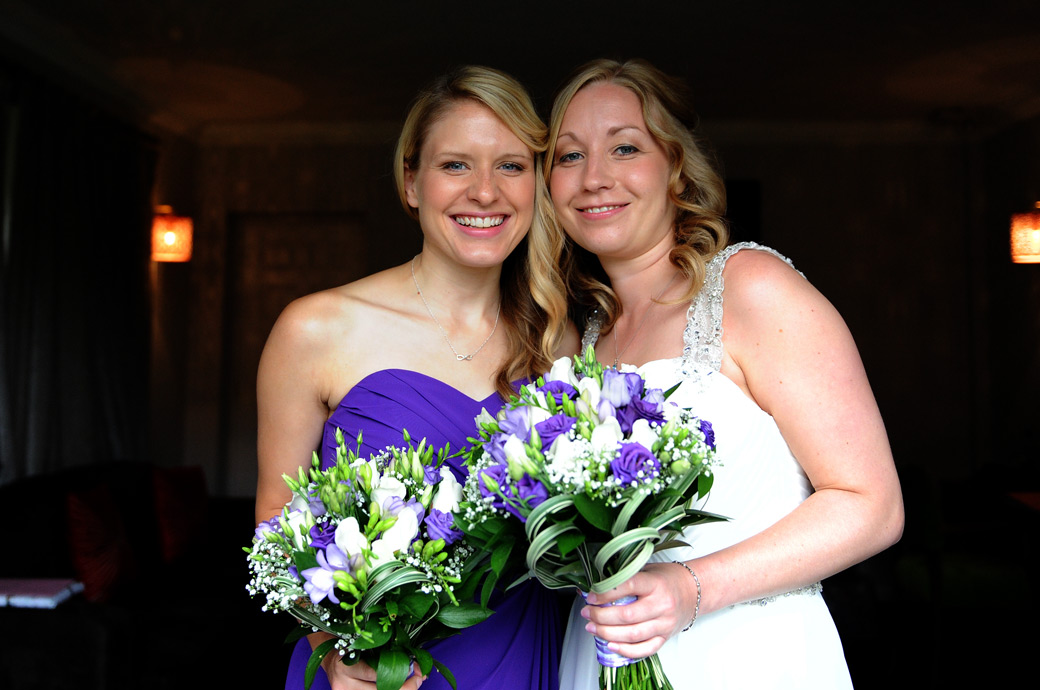 Smiling Bride and Bridesmaid pose for the Surrey Lane wedding photographer after getting ready in the Tennyson Room at the pleasant and relaxed Lythe Hill Hotel Haslemere