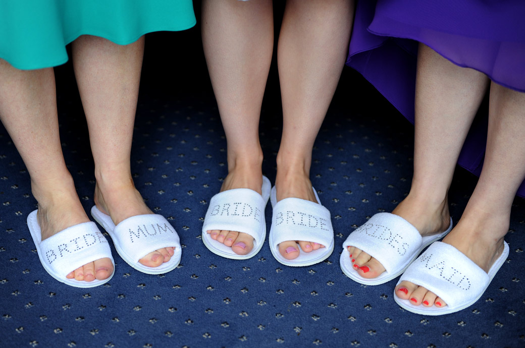 A wedding photograph of the Bride, her mother and her Bridesmaid's feet in their named slippers  captured at Surrey wedding venue Lythe Hill Hotel in the Tennyson Suite