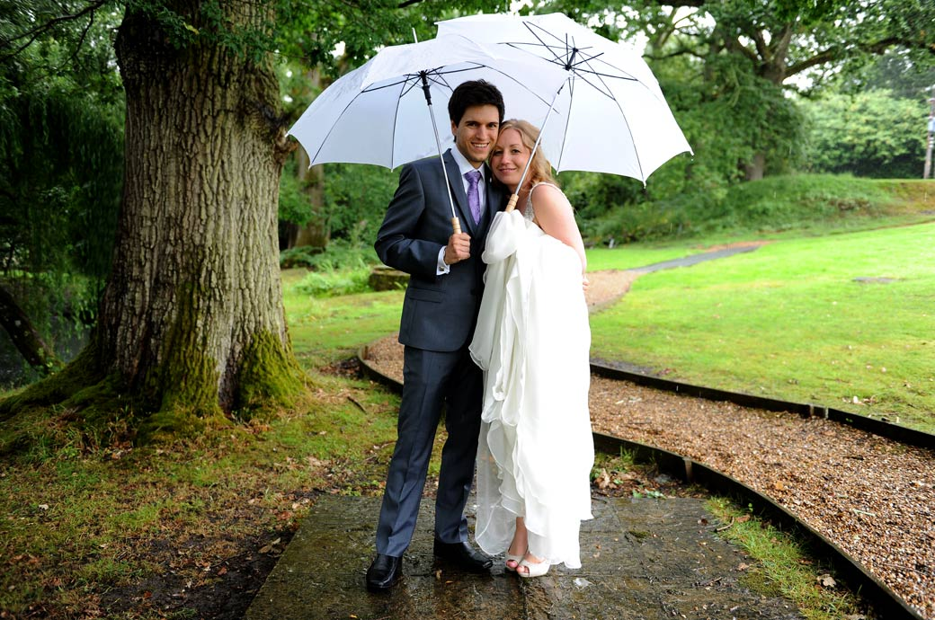 Lovely newlywed wedding picture taken in the grounds of Surrey wedding venue Lythe Hill Hotel as they shelter from the heavy rain under white umbrellas