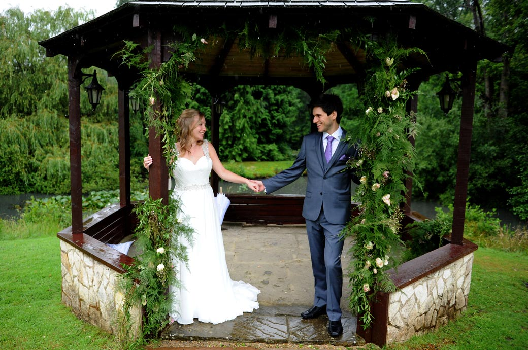 Loving tender smiles and looks as the Bride and groom touch hands standing at the entrance to the gazebo out of the rain at the Lythe Hill Hotel wedding venue Surrey