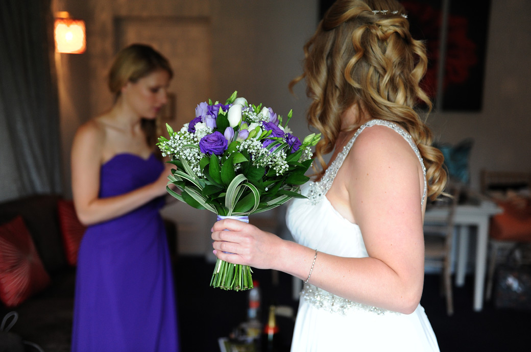 A wedding picture of the Bride looking to her Bridesmaid as she holds her beautiful flower bouquet at Lythe Hill Hotel Surrey in the outside Tennyson Suite