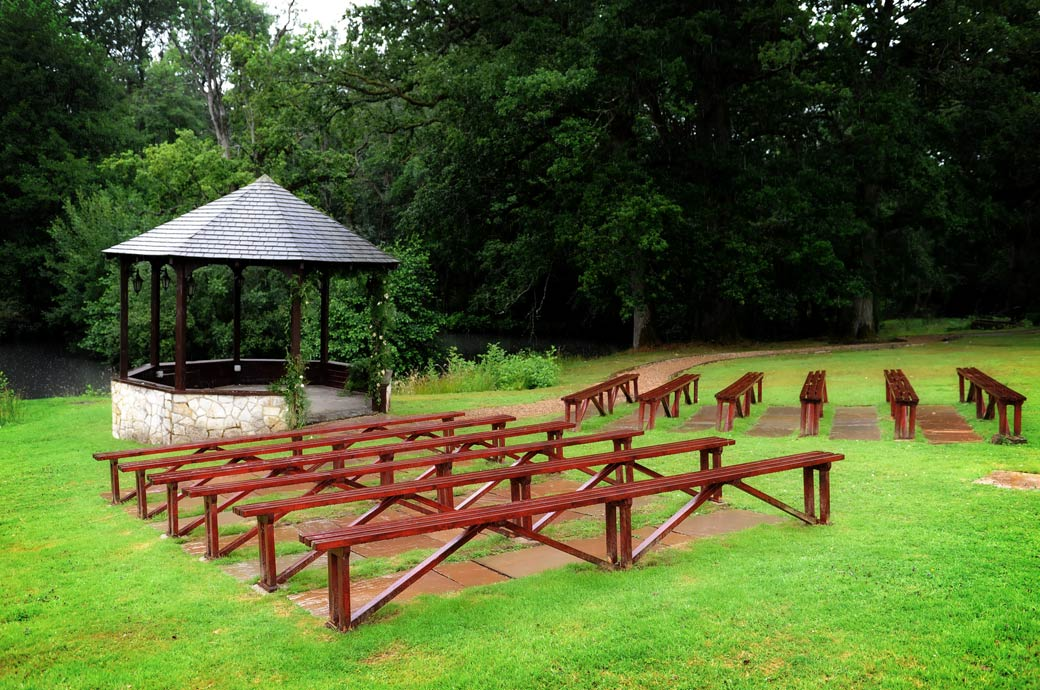 The wet wooden benches on the main lawn in front of the gazebo captured in this wedding photograph on the wet morning of a wedding day in Surrey at  Lythe Hill Hotel