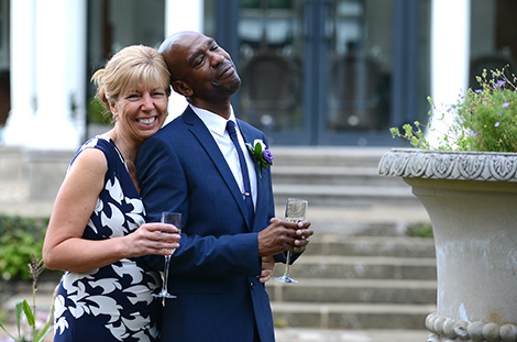 Delightful wedding photograph of a newly married couple enjoying champagne at Cannizaro House in Wimbledon after their Morden Park House wedding ceremony in Surrey
