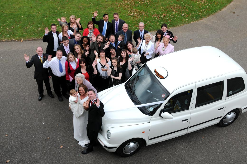 Everyone standing around a white taxi wedding car and waving captured from the first floor of Morden Park House after a Merton Register Office marriage ceremony