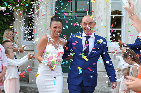 Wedding couple at the front of Surrey wedding venue Merton Register Office in Morden Park House getting covered in a shower of brightly coloured confetti