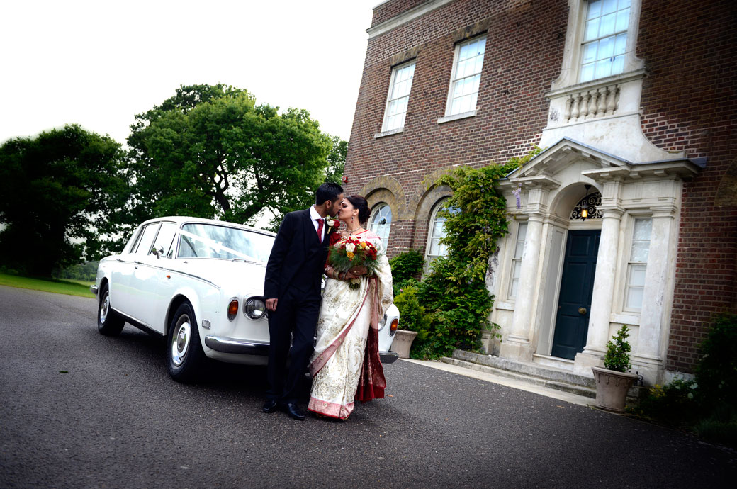 Romantic kiss in front of a white Rolls Royce wedding photo taken at the Surrey wedding venue Merton Register Office, Morden Park House