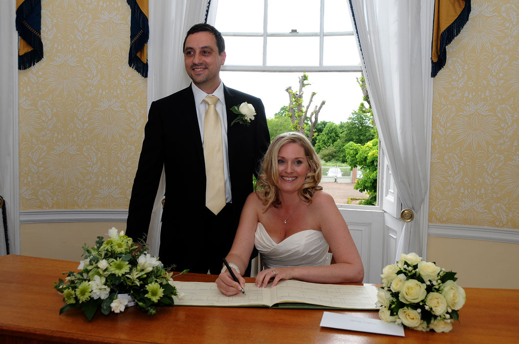 Smiling Bride with her beaming Groom at Surrey wedding venue Merton Register Office in Morden Park House sign the marriage register in the Lord Nelson Room
