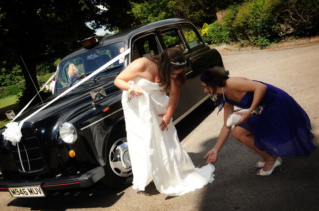 Adjusting the Bride's dress as she leaves the Black cab in this wedding picture taken at Surrey wedding venue Nonsuch Mansion