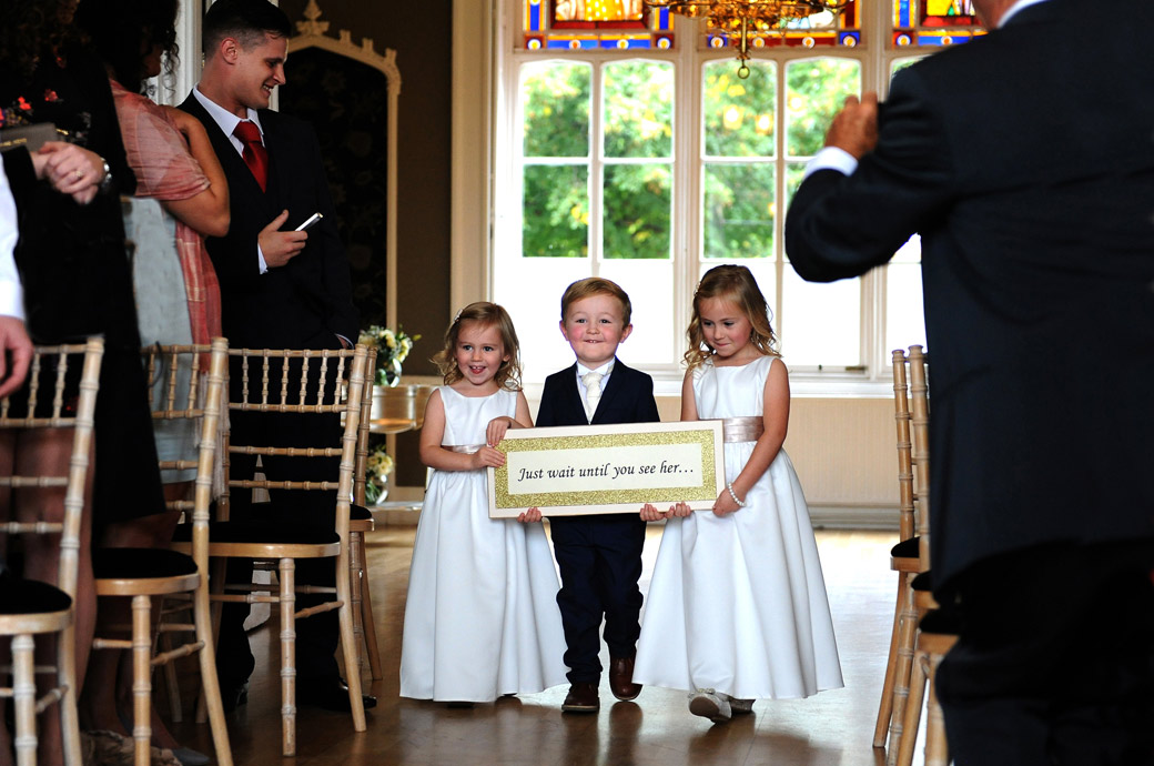 Cute wedding photo of pageboy and two flower girls holding up a signboard at Surrey wedding venue Nonsuch Mansion as they walk down the aisle of the Orchid Room