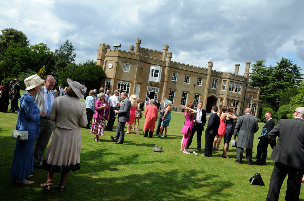 Lovely, colourful summer wedding photograph of relaxed guests drinking out on the lawn by Surrey Lane wedding photography at  Nonsuch Mansion, Cheam