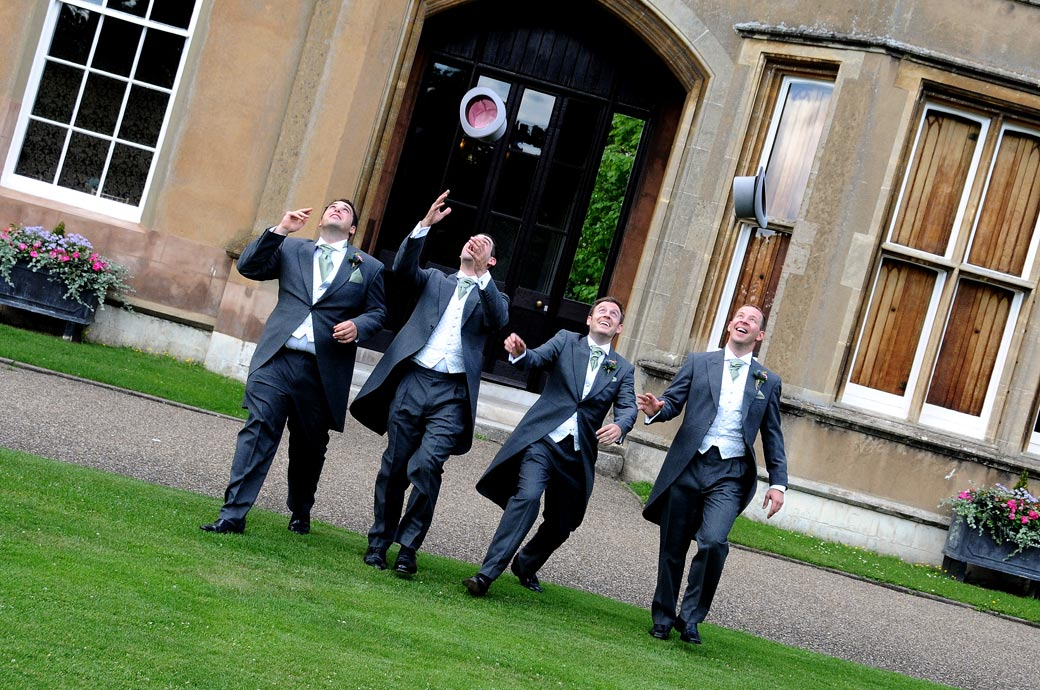 Groom and Groomsmen have fun throwing their top hats into the air in relaxed pre wedding photo taken on the lawn of the Surrey wedding venue Nonsuch Mansion