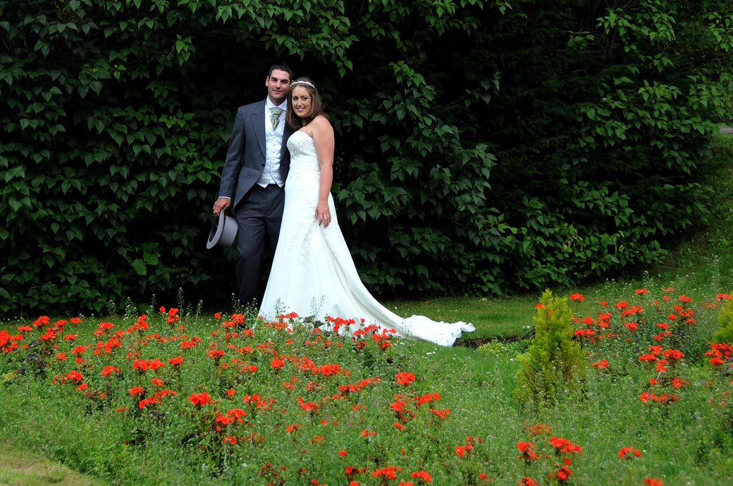Wedding photo of happy and radiant newly-weds standing together on a lawn full of bright red poppies at Nonsuch Mansion taken by Surrey Lane wedding