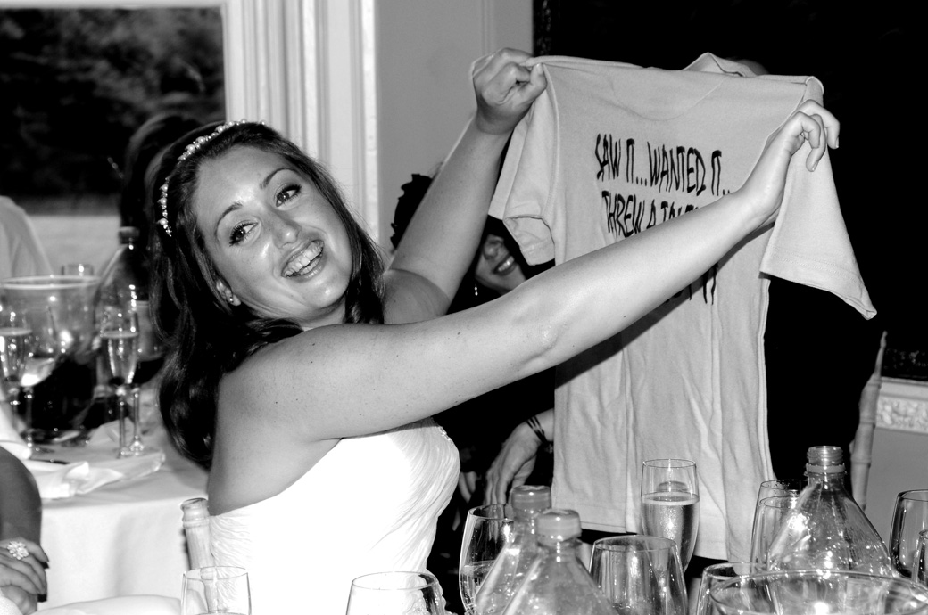 Bride enjoying the moment as she is presented with a joke tee-shirt during the wedding speeches in the Orchid Room at Nonsuch Mansion Surrey near Cheam Village