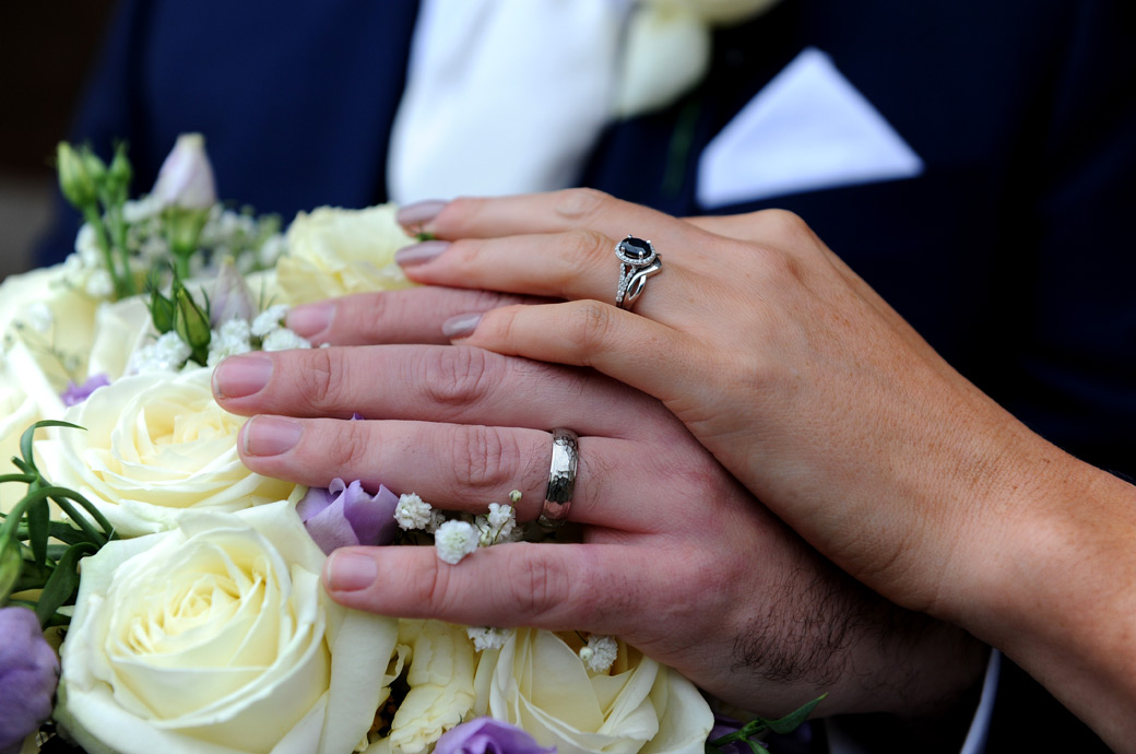 Wedding rings on show for the newlywed couple as they take a break from their walk in the lovely grounds of historic Surrey wedding venue Nonsuch Mansion