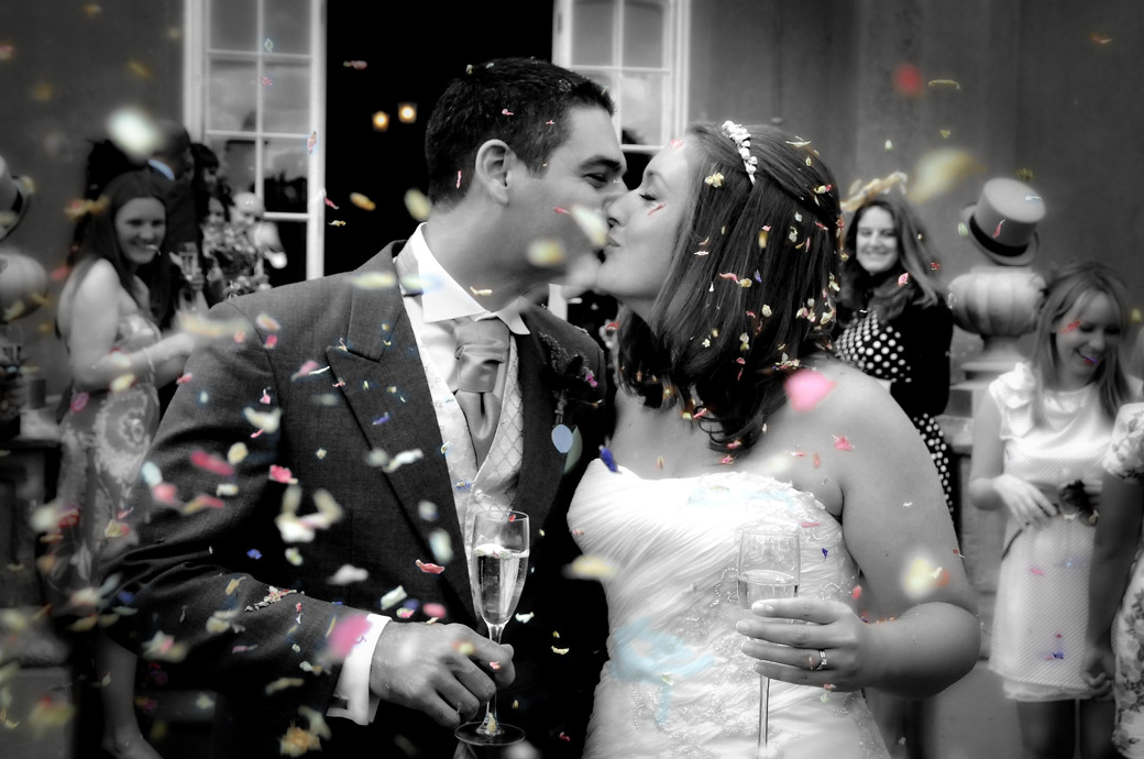 A wonderful romantic and happy kissing moment photo captured as the confetti falls taken by Surrey Lane wedding photography at Nonsuch Mansion, Cheam