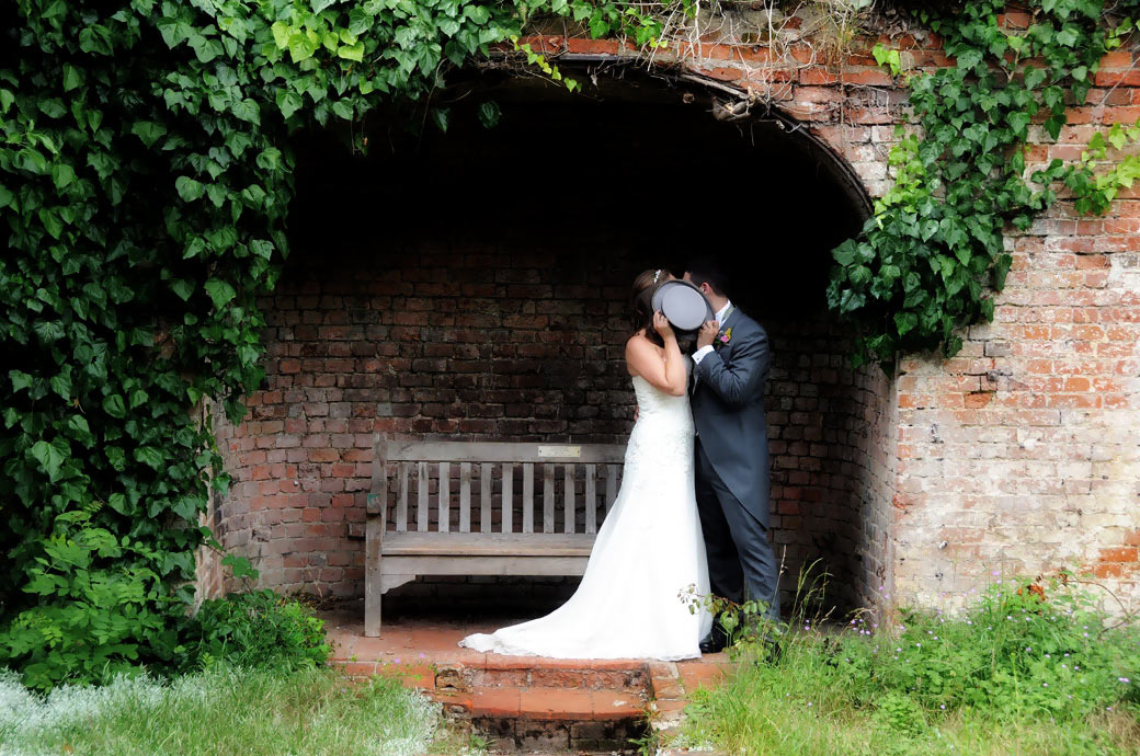 The Bride and Groom take a delightfully discrete kiss behind the Groom's Top Hat in an archway by Surrey Lane wedding photography at Nonsuch Mansion