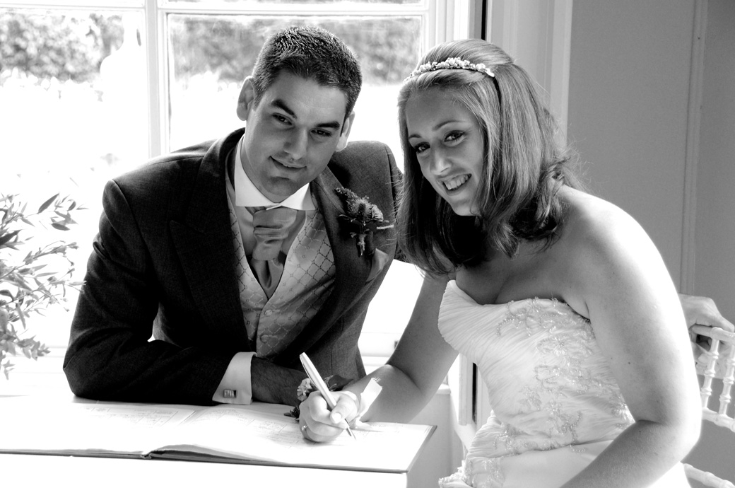 Smiling for the cameras in this signing the register wedding picture taken at Surrey wedding venue Nonsuch Mansion in the Orchid Room