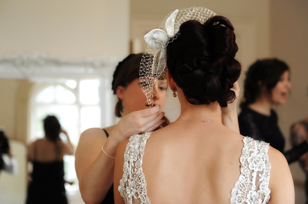 Wedding photo of a bride having her fascinator adjusted as she finishes getting ready in the bridal suite at Nonsuch Mansion a Surrey wedding venue situated in Cheam village