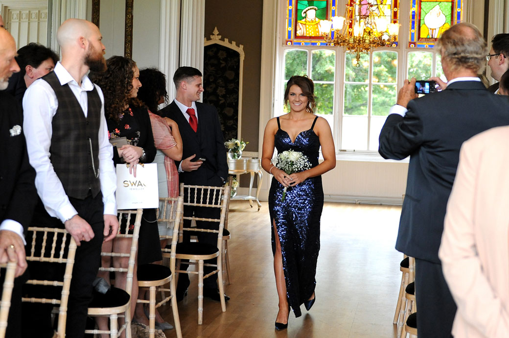 All smiling sister bridesmaid walks down the aisle in her sparkling dress in this lovely wedding picture taken at surrey wedding venue Nonsuch Mansion in the Orchid Room
