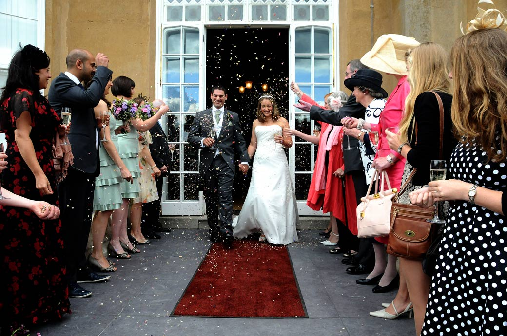 Bride and Groom walk the red carpet to get covered in confetti at Nonsuch Mansion by Surrey Lane wedding photographers