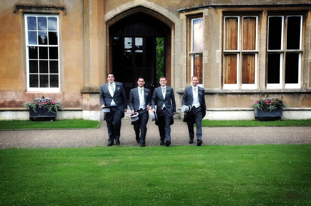 Hats in hand as the Groom and his Groomsmen walk across the lawn to the wedding photographer at Nonsuch Mansion a Surrey wedding venue with a long history