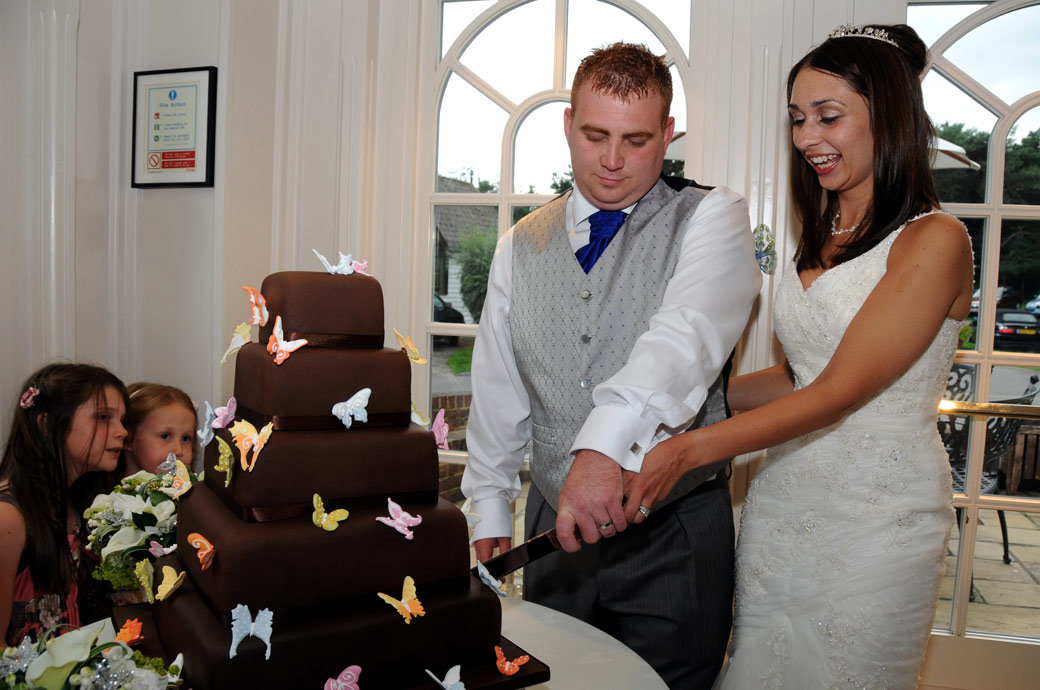 Bride and Groom get stuck into cutting the wedding cake at the lovely Surrey wedding venue Oaks Farm Weddings in the Orangery room