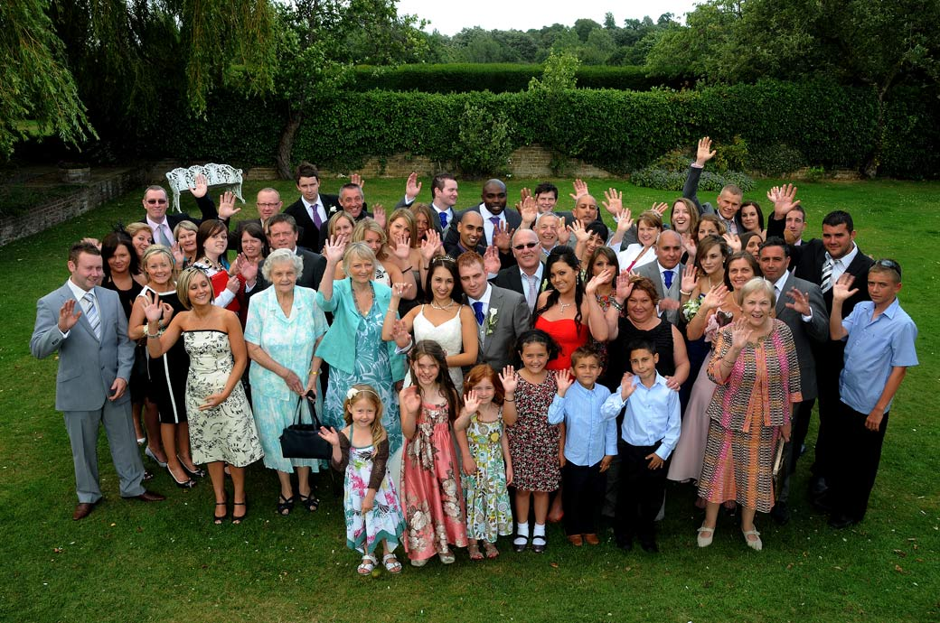 Everyone at the wedding waving at the photographer in this picture taken at Oaks Farm Weddings a little Surrey wedding venue in a lovely setting