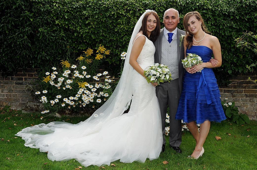 A proud Father of the Bride posing with his two daughters at Surrey wedding venue Oaks Farm Weddings out in the lovely gardens
