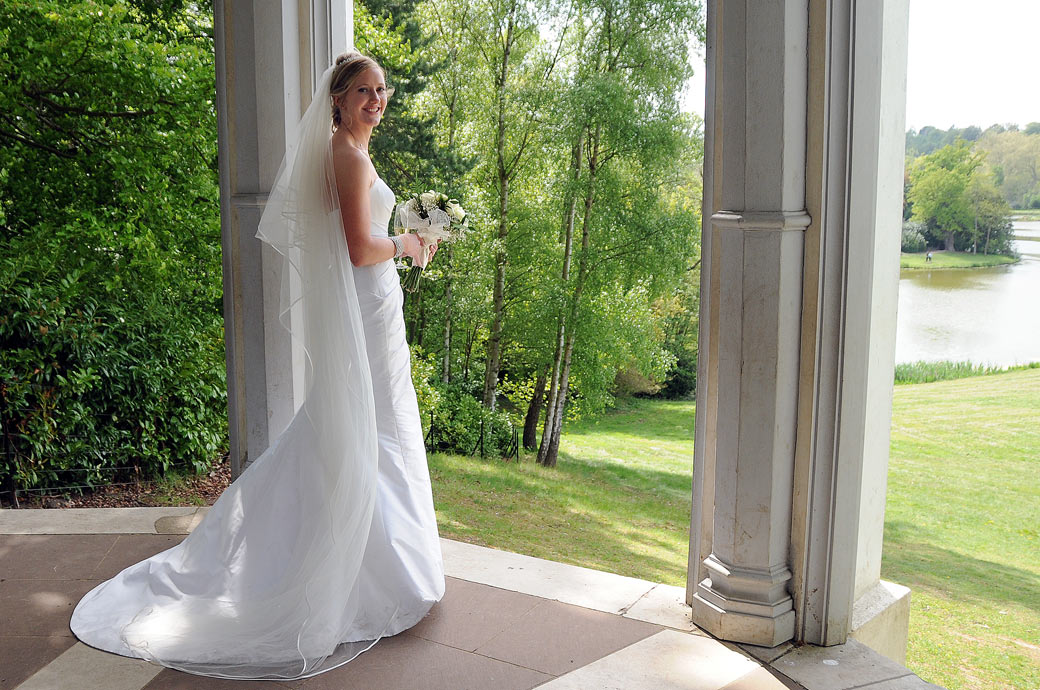 A beautiful Bride standing alone in the must see Gothic Temple with its wonderful views over Painshill Park Cobham captured by Surrey Lane photography