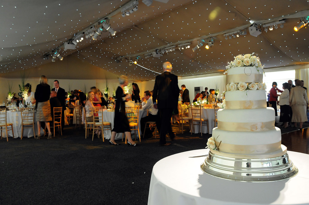 An atmospheric wedding photo taken from behind the wedding cake by Surrey Lane wedding photography in the marquee at Painshill Park wedding venue